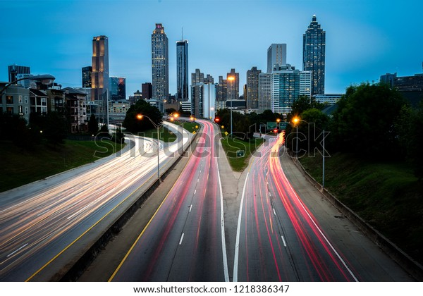 Atlanta skyline during sunset shot from Jackson Street Bridge with light trails of cars during rush hour