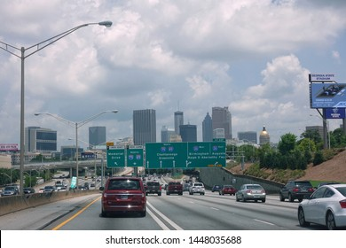 Atlanta,GA/USA-7/6/19: Cars going north on interstate highways 75 and 85 leading to downtown Atlanta with a hazy view of the city.