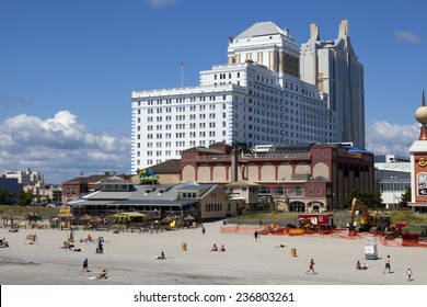 Atlantic City, New Jersey, USA - Aug 24, 2014: Tourist enjoying the beach in front of the Resorts Casinos with Jimmy Buffett's Margaritaville restaurant in Atlantic City, New Jersey. on Aug 24, 2014