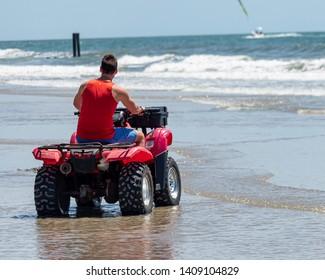 Atlantic City, NJ / USA - May 25, 2019: Atlantic City Life Guard Riding Quad on the Beach