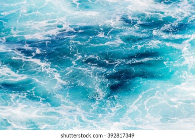 Atlantic ocean with blue water on a sunny day. Waves, foam and wake caused by cruise ship in the sea