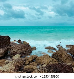 The Atlantic Ocean during winter time in Freeport, Bahamas with turquoise waters that are crashing on the riprap.