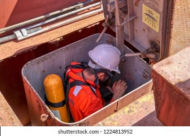 Atlantic Ocean, near coast of Guatemala - February 10, 2018: Seaman during fire emergency training drill, on board merchant cargo ship, wearing fire fighting equipment, breathing apparatus and helmet