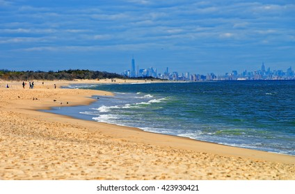 Atlantic Ocean shore at Sandy Hook with view on NYC. Sandy Hook is in New Jersey, USA. Tourists on the shore