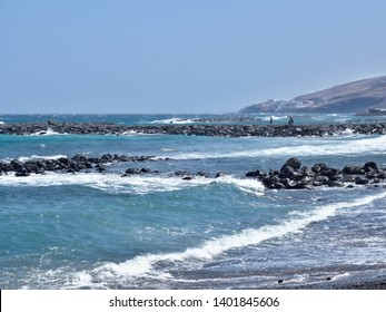 The Atlantic throws white foamy waves on the beach, wave breakers built of volcanic rock go into the sea, you can see a part of the south coast. Two people walk far away and unidentifiable