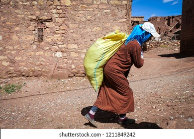 Atlas Mountains, Morocco - October 4, 2018: Old berber woman is carrying large yellow bag in a traditional berber village in the mountains in Morocco