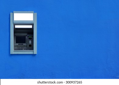 ATM Or ABM Or Cashpoint Machine Or Hole In The Wall Byilt-In The Blue Concrete Wall Textured Background With Copy Space