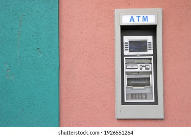 An ATM banking machine set into a colorful concrete wall