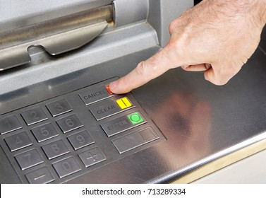 An ATM button keypad with a finger pressing the CANCEL button