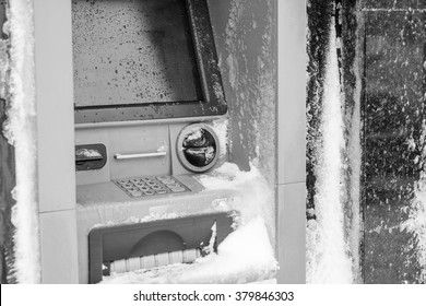 Atm machine covered with snow. Black and white picture of functional bank atm machine covered with ice and snow.