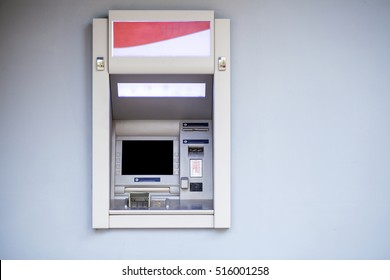 ATM in the mall without people, gray wall outdoors