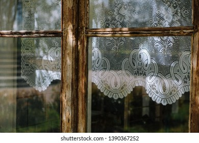 Atmoshperic play of light on vintage historical wooden window with white crochet kitchen curtains. White embroider curtains behind the window with traditional patterns. Window needs to be restored.