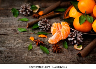 The atmosphere of Christmas and New Year: Fresh tangerine with green leaves on a dark wooden background. Mandarin peeled and disassembled into slices, cinnamon sticks, cones, tangerine peels, leaves.