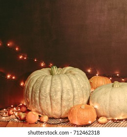 Atmosphere Halloween composition with pumpkins apples and light garland. Autumn background
