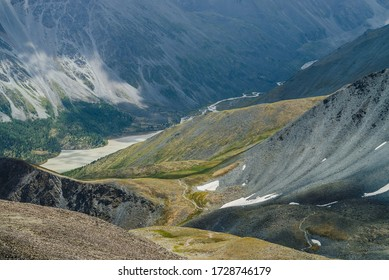 Atmospheric alpine landscape with beautiful valley with mountains lake and giant textured slopes with nature patterns. Awesome aerial view to big rocky hills and huge mountains. Forest on mountainside