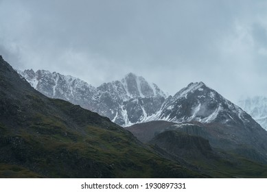 Atmospheric alpine landscape with great mountain peaked top with snow in low clouds. Dramatic mountain scenery with sharp pinnacle in overcast weather. Awesome view to snowy pointy peak in cloudy sky.