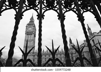 Atmospheric black and white photos of big ben framed by ornate gothic wrought iron fencing around Westminster Palace in London