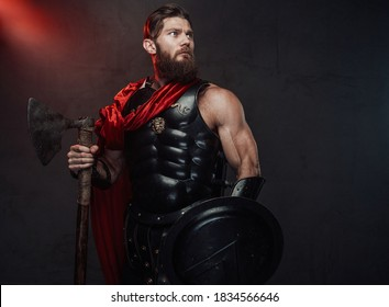 Atmospheric and dark room with spotlight and roman guardian with muscular build and beard holding axe and shield whihc posing in it.