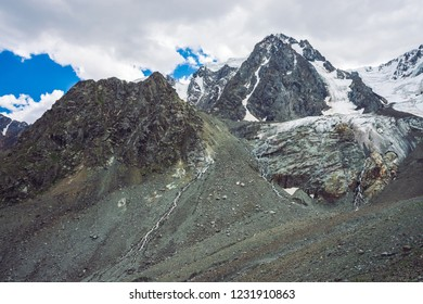 Atmospheric giant snowy mountains. Icy rocks with waterfall. Water stream from glacier. Dark rocky mountainside with ice. Snow on mountain ridge. Unusual landscape of majestic nature of highlands.