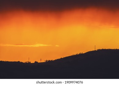 Atmospheric landscape with dark silhouette of mountain with trees on background of vivid orange dawn sky. Colorful nature scenery with sunset or sunrise of illuminating color. Vivid sundown paysage.