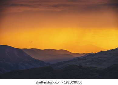 Atmospheric landscape with silhouettes of mountains and hills with trees on background of orange dawn sky. Colorful nature scenery with sunset or sunrise of illuminating color. Sundown paysage.