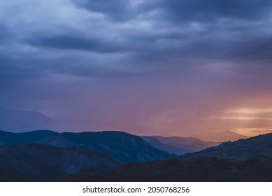 Atmospheric landscape with silhouettes of mountains on background of vivid dawn sky. Colorful nature scenery with sunset or sunrise of orange blue magenta violet pink lilac color. Sundown paysage.