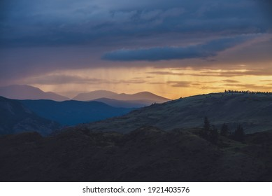 Atmospheric landscape with silhouettes of mountains with trees on background of vivid orange blue violet dawn sky. Colorful nature scenery with sunset or sunrise of illuminating color. Sundown paysage