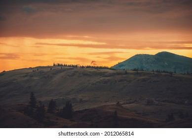 Atmospheric landscape with silhouettes of mountains with trees on background of orange dawn sky. Colorful nature scenery with sunset or sunrise. Sundown paysage in vintage colors and faded tones.