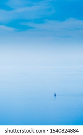 Atmospheric misty blue ocean view with  distant yacht seemingly lost and insignificant between sky and sea