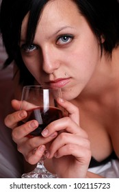 Atmospheric picture with a lady at bed holding a glass of red wine