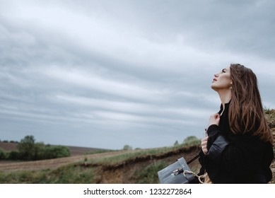 Atmospheric Portrait of a girl on a background of a cloudy sky before the rain. Psychological portrait. Dissonance, depression, longing, fear, loss, past