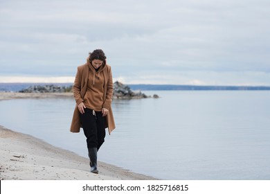 Atmospheric portrait of a young woman in  stylish clothers on a sandy beach near a blue sky on a autumn day. The concept of female freedom and emancipation