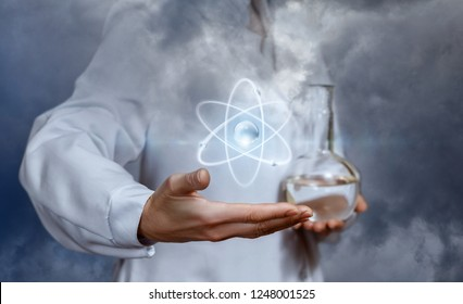 The atom is flying above a hand of a laboratory assistant who is keeping a flask with transparent substance in an other one. The concept is the interaction of different studies.