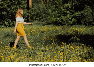 Atractive blonde girl walking across the dandellions field.. Natural beauty, yellow skirt and white croptop. Ecology gardening, self-care, healthy lifestyle, wellness, parkland. Selective focus, copy