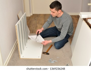 Atractive male assembling a cupboard on the floor - reading instructions.