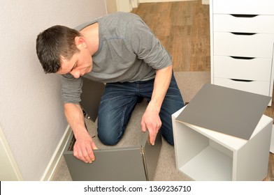 Atractive male assembling a cupboard on the floor