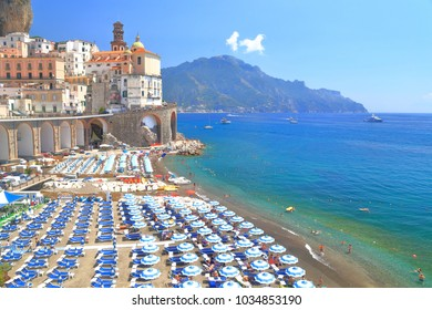 Atrani village and sunny beach umbrellas by the sea on Amalfi coast, Italy