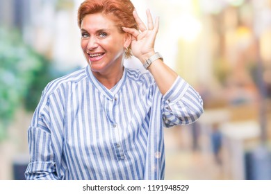 Atrractive senior caucasian redhead woman over isolated background smiling with hand over ear listening an hearing to rumor or gossip. Deafness concept.