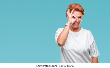 Atrractive senior caucasian redhead woman over isolated background doing ok gesture with hand smiling, eye looking through fingers with happy face.