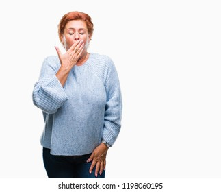 Atrractive senior caucasian redhead woman wearing winter sweater over isolated background bored yawning tired covering mouth with hand. Restless and sleepiness.