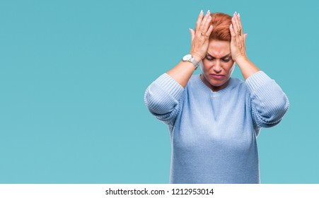 Atrractive senior caucasian redhead woman over isolated background suffering from headache desperate and stressed because pain and migraine. Hands on head.