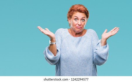 Atrractive senior caucasian redhead woman wearing winter sweater over isolated background clueless and confused expression with arms and hands raised. Doubt concept.