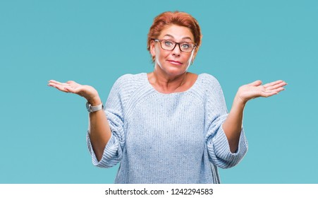 Atrractive senior caucasian redhead woman wearing glasses over isolated background clueless and confused expression with arms and hands raised. Doubt concept.