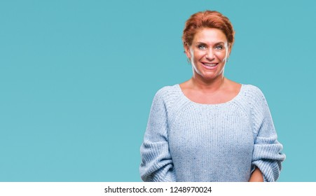Atrractive senior caucasian redhead woman wearing winter sweater over isolated background with a happy and cool smile on face. Lucky person.