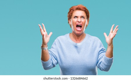 Atrractive senior caucasian redhead woman over isolated background crazy and mad shouting and yelling with aggressive expression and arms raised. Frustration concept.