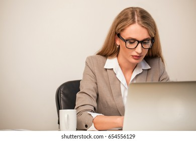 Atrractive young businesswoman typing. Woman sitting in the office and wearing suit.