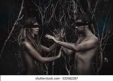 atrractive young man and woman with eyes closed. lost in forest.