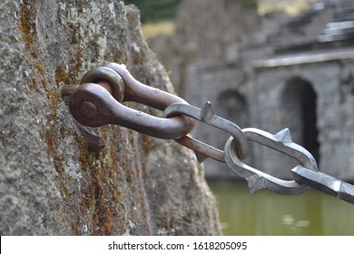 Attaching a metal chain to a large stone. Connecting the rigging bracket to the anchor bolt
