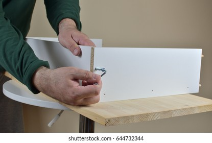 Attaching two particle boards with a screw using Allen key - close-up