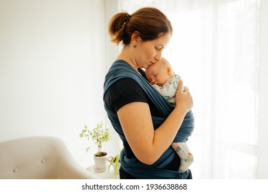 Attachment parenting concept. Young mother with baby in sling